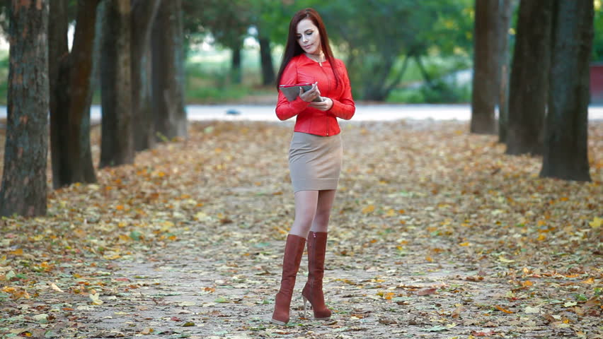 Young woman wearing red leather jacket with tablet computer in autumn park. Long shot - HD stock footage clip