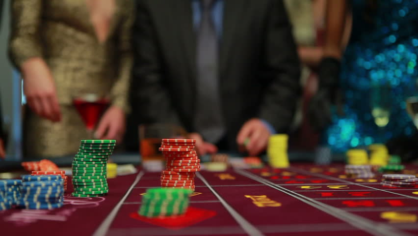 People placing their bets on the roulette table in the casino