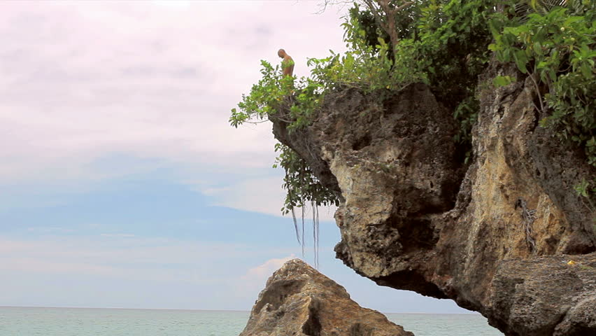 Man dives off a cliff into the ocean - HD stock footage clip