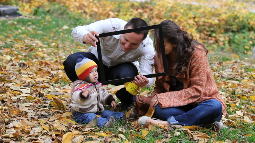Happy young family sitting on autumn leaves and shooting in a picture frame - HD stock video clip