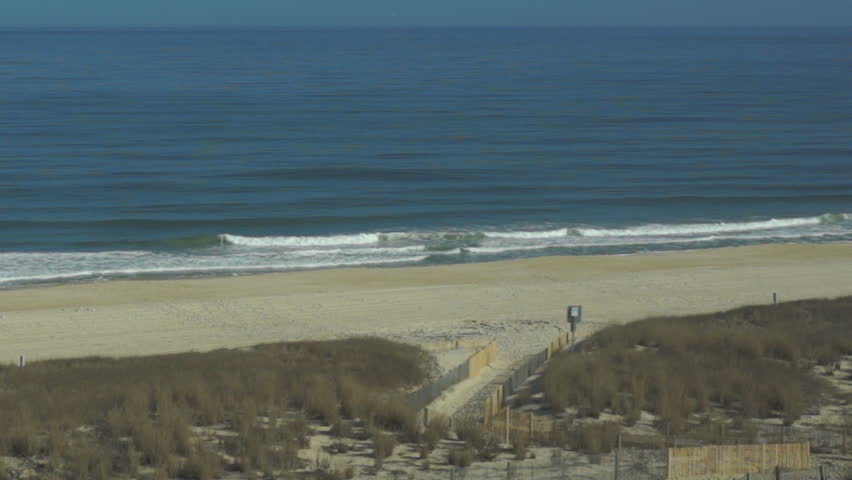 Welcoming Beach A Dune Path Of Sand Cuts Through And Opening In A Fence To T