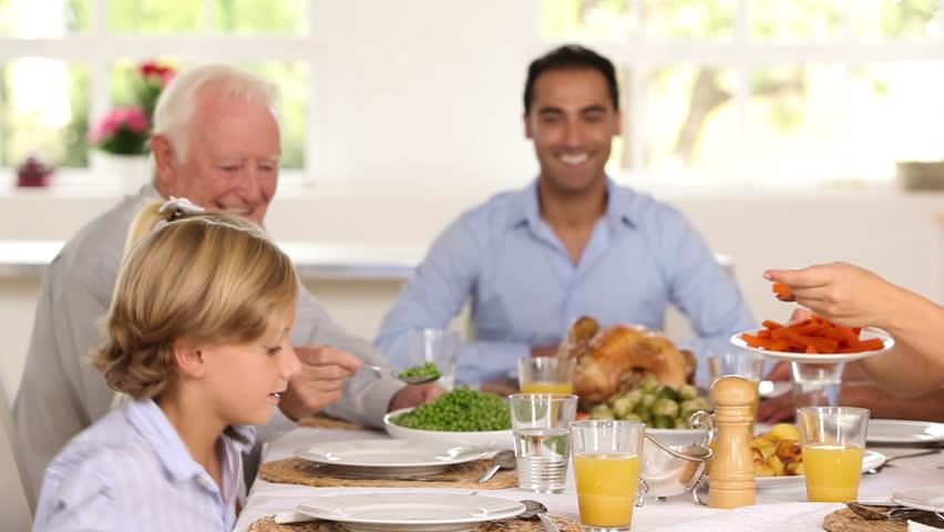 Smiling mother serving up carrots for son at family dinner around dinner table
