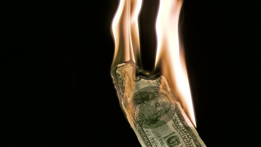 Fire in super slow motion burning a bank note against a black background