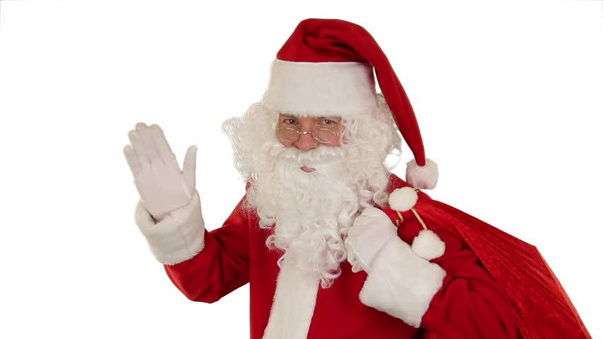 Santa Claus carrying his bag, looks at the camera sends a blow kiss and wave,