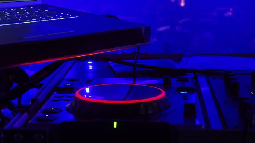 dj equipment  people dancing background against blue light