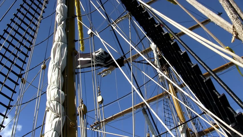 Mast, rigging with pirate flag from deck of Indonesian tall ship Dewaruci against blue sky  