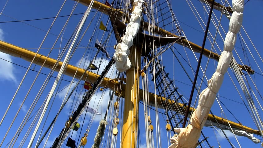 Masts, rigging, banners and flags on Indonesian tall ship Dewaruci against blue sky and clouds   
