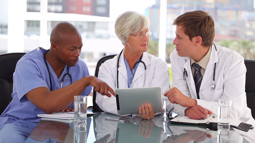 Mature doctor using a touchscreen with her colleagues in a bright office - HD stock footage clip