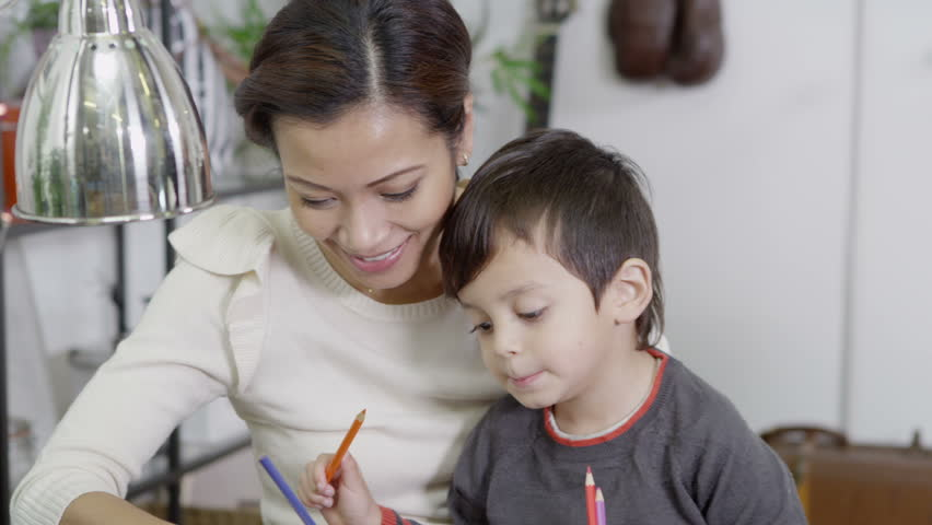 A mother and her cute young son spend time together at home, drawing and writing with colored pencils. In slow motion.