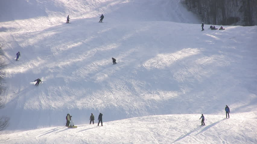 People Skiing And Snow Boarding Down A Ski Mountain