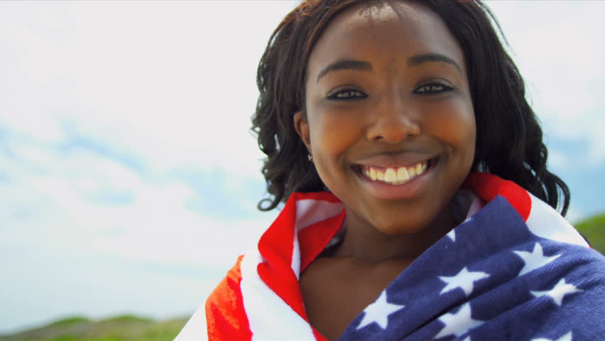 African American Beach Girl wrapped in American Flag. Slow motion. - HD stock video clip