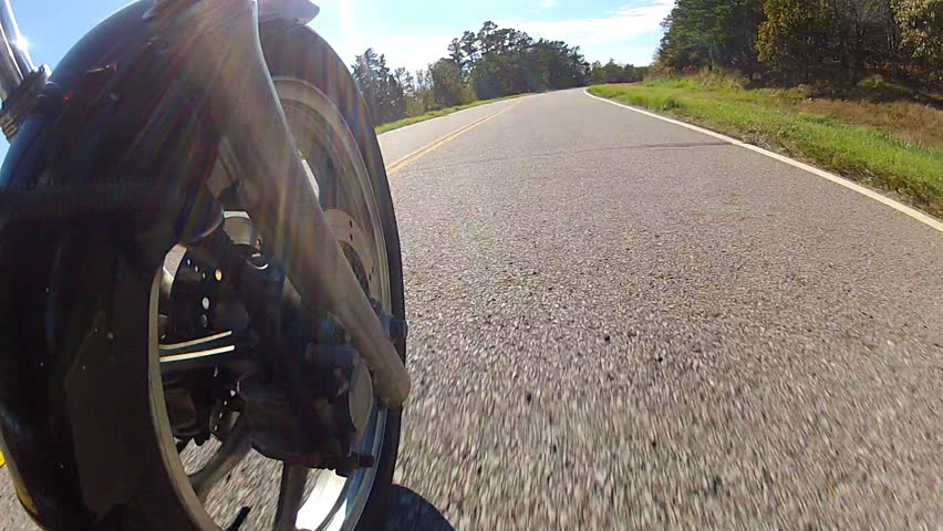 A point of view shot of a speeding motorcycle with the camera places just behind the front wheel. The motorcycle is traveling down on a forested mountain road in Oklahoma, USA. - HD stock footage clip