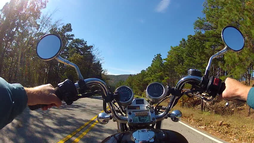 A wide angle point of view shot from a chest mounted camera on a motorcyclist riding a motorcycle on a forested mountain road.
