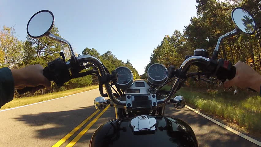 A wide angle shot of the point of view of someone riding a motorcycle on a forested mountain road. - HD stock video clip