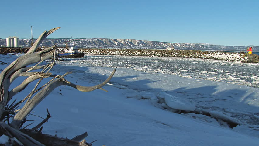 Working tug Redoubt leaves icy Homer Harbor on yet another mission. - HD stock footage clip