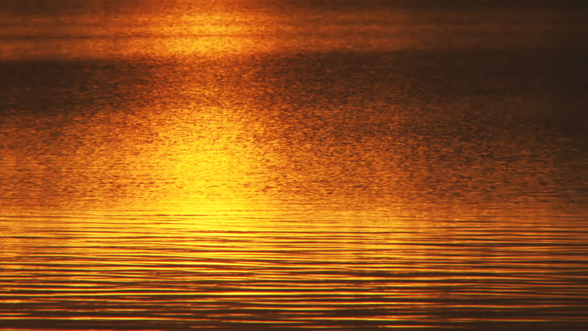 Resplendent sunset reflected off a lake's varied and soothingly patterned surface in the late evening in midsummer Alaska. - HD stock footage clip