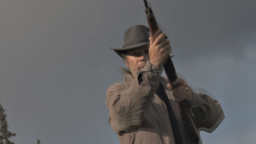 Sinister-looking man in a beat up black hat getting ready to shoot ... POV shot