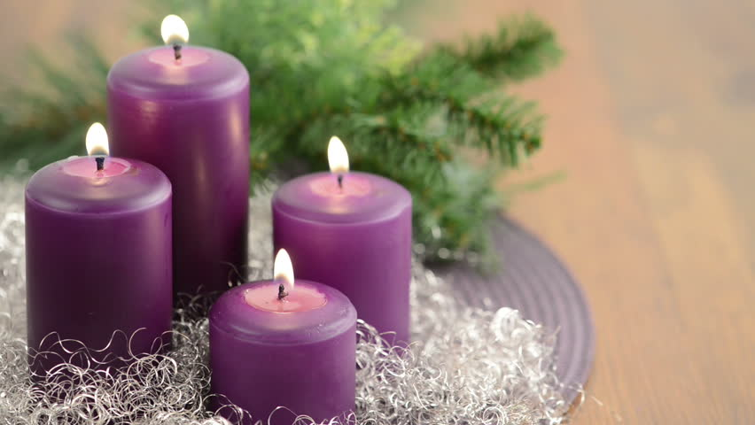 ... with purple Advent candle burning with wreath and silver decoration