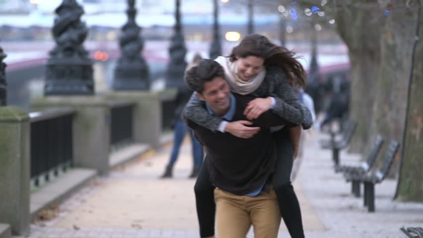 Piggyback. Casually dressed heterosexual couple having fun together in a big city. They are running and laughing. - HD stock footage clip