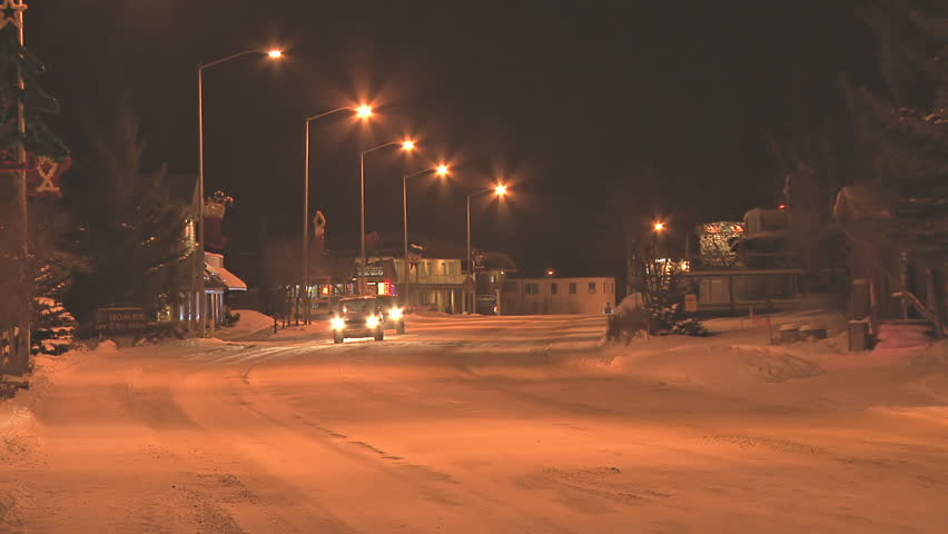 HOMER, AK - CIRCA 2011: Minimal traffic at night in a small town on snow-covered roads in the middle of winter. - HD stock footage clip