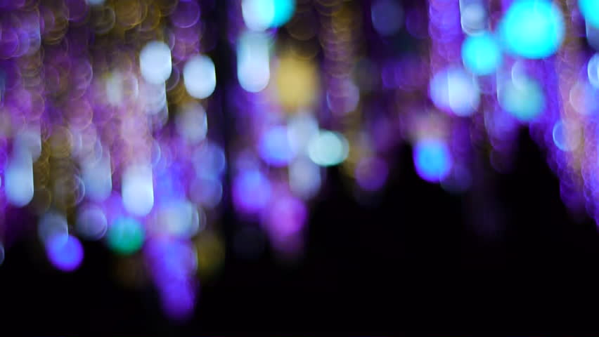 Silhouettes pass under a dazzling array of colorful flashing lights. | Shutterstock HD Video #3174292