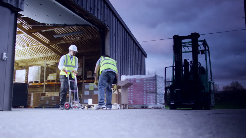 2 men in high visibility clothing are outside an open warehouse, stacking boxes onto a pallet. It is starting to get dark and the two men shake hands upon completion of the job. In slow motion.