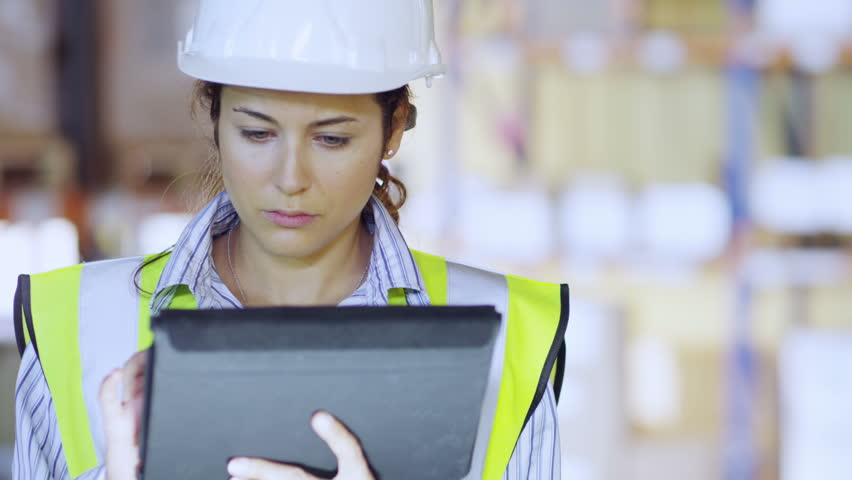 An attractive female warehouse employee wearing high visibility clothing and a hard hat is working on a digital tablet and checking stock levels. Other employees can be seen working in the background