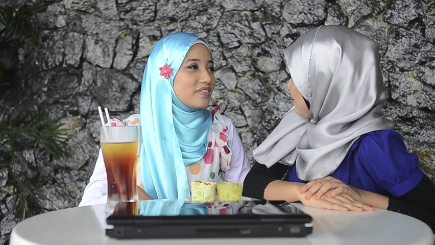 Two young pretty Asian muslim business woman in head scarf at cafe - HD stock footage clip