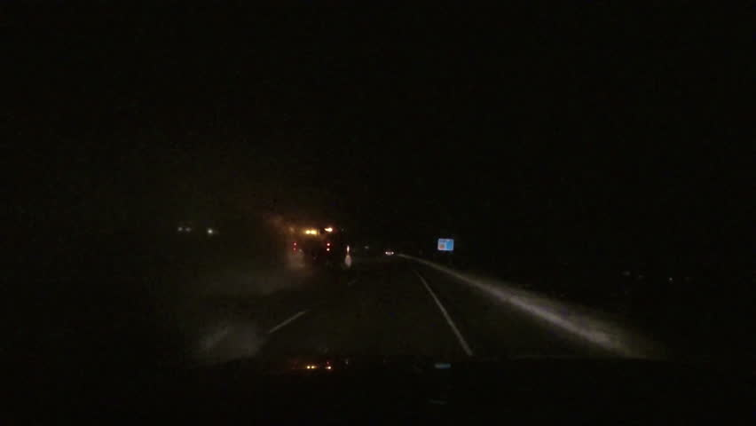 Night snow storm traffic plow driving POV. Winter snow blizzard with ice and snow on road. First person point of view (POV) looking through drivers windshield. - HD stock footage clip