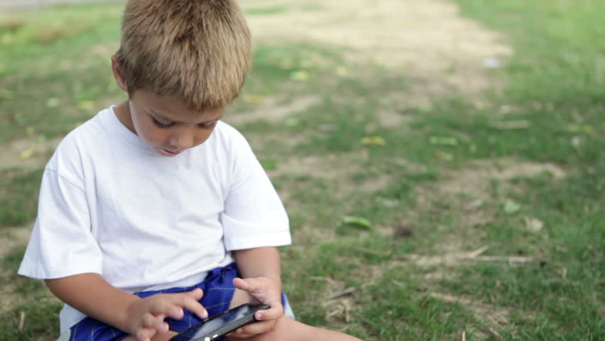 Child busy playing on cell phone in grass - HD stock video clip