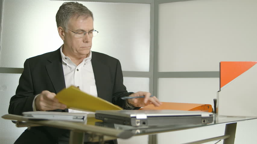 A fatigued man working at his desk removes his glasses and shows symptoms of headache. - HD stock footage clip