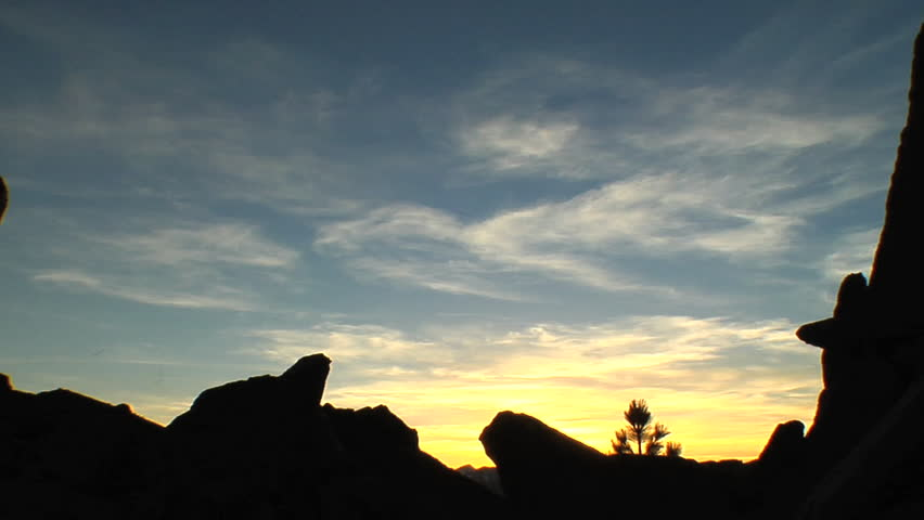 Silhouette of a man with a backpack taking pictures of nature on rocky terrain in the mountains of the American wilderness