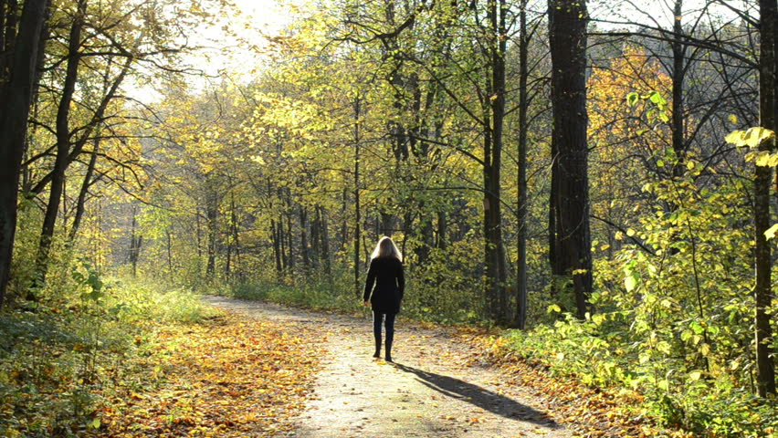 Blond Woman Walk On Autumn Forest Road Covered With