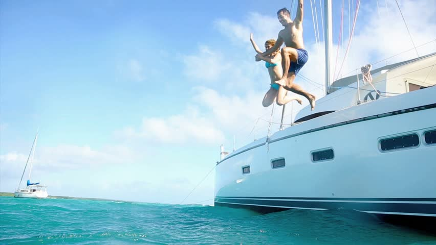 Young couple jumping in water from yacht