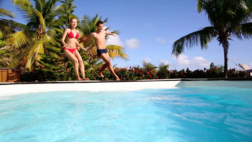 Young couple jumping in swimming pool