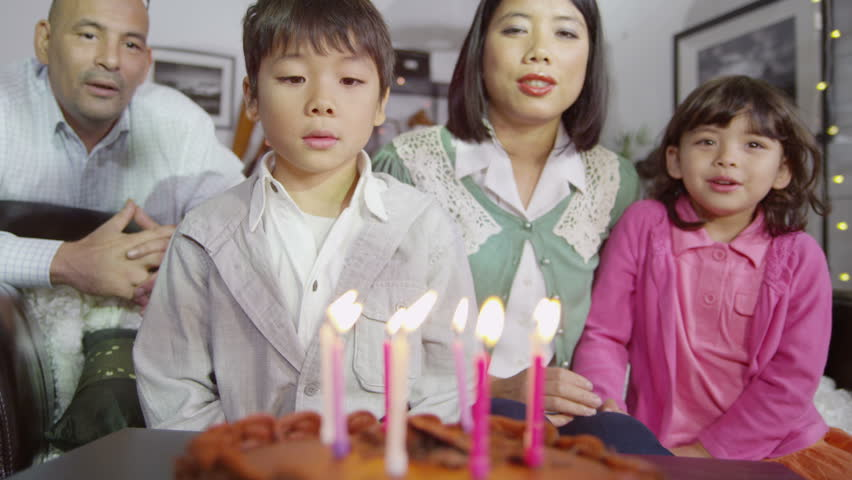 Cute young boy tries to blow out all the candles on his birthday cake but can't do it with just one breath so his family cheer him on and applaud him. In slow motion.