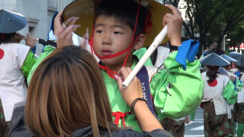 NAGOYA, JAPAN - 20 OCTOBER 2012: A girl with long pink fingernails fixes the cone hat of a boy taking part in the Nagoya Matsuri (festival) in Japan - HD stock video clip