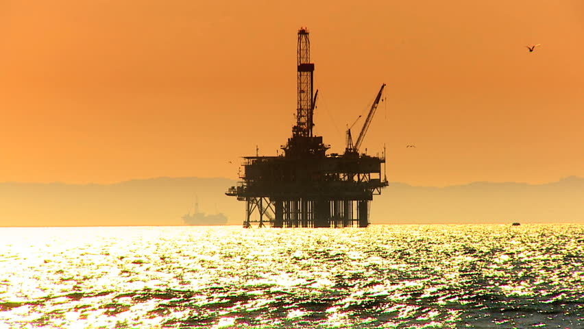 Oil platform in the sea at sunset - HD stock video clip