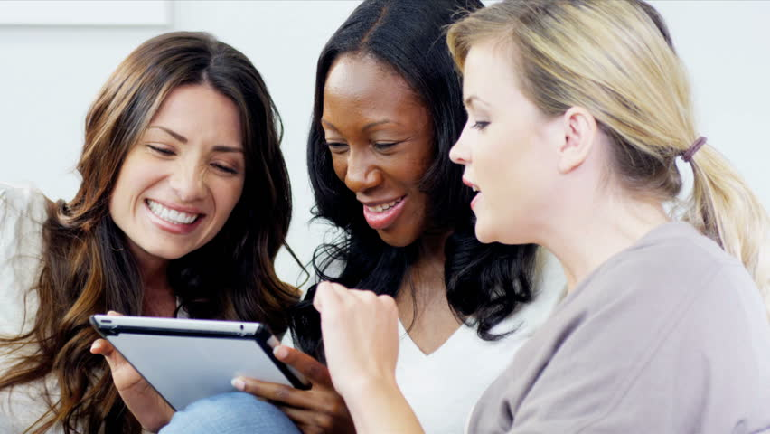 Caucasian and African American pretty female friends planning holiday on the Internet using tablet computer interior shot on RED EPIC