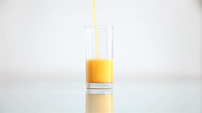 Fresh orange juice flowing in a glass