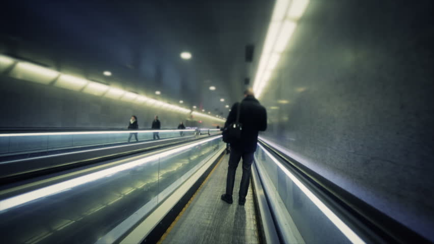 Person passing in flat escalator at metro station