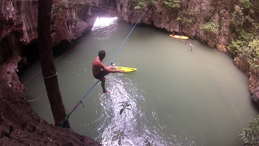 A flute player helps a climber cross a slack line that is set up over a tropical lake