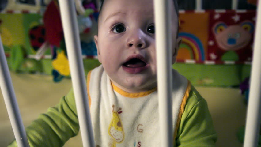 Cute boy smiles in baby crib - HD stock video clip