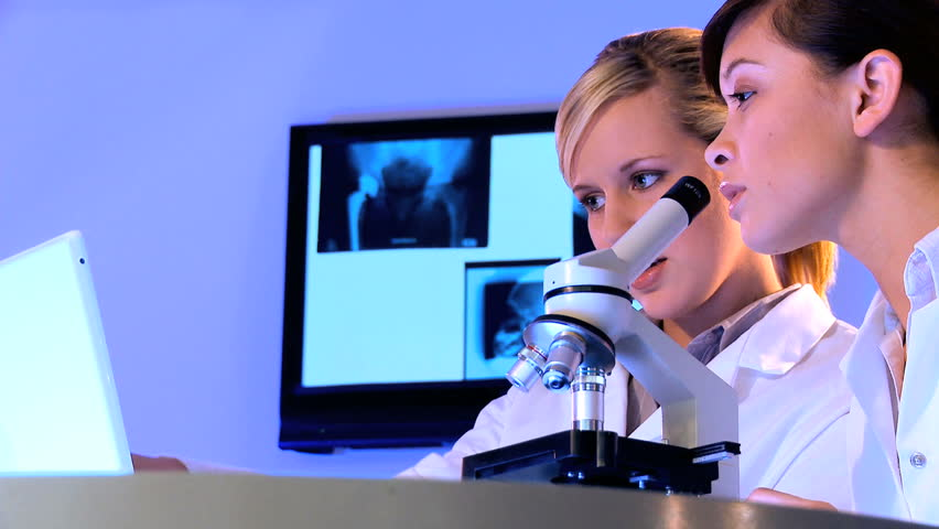 Medical students using professional scientific approach with microscope - HD stock video clip