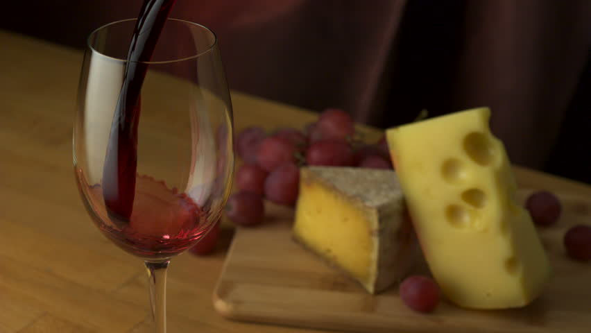 Pouring red wine into glass with grape and cheese shooting with high speed camera, phantom flex. - HD stock footage clip