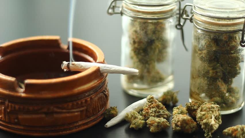 Marijuana Joint Burning 1. A marijuana filled joint burning on the edge of a wooden ashtray. Jars of marijuana and more around.