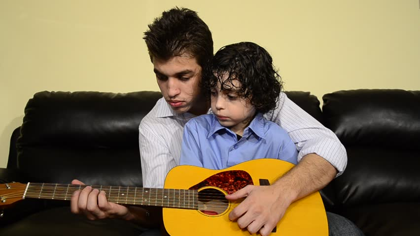 Elder brother teaching his sibling to play guitar