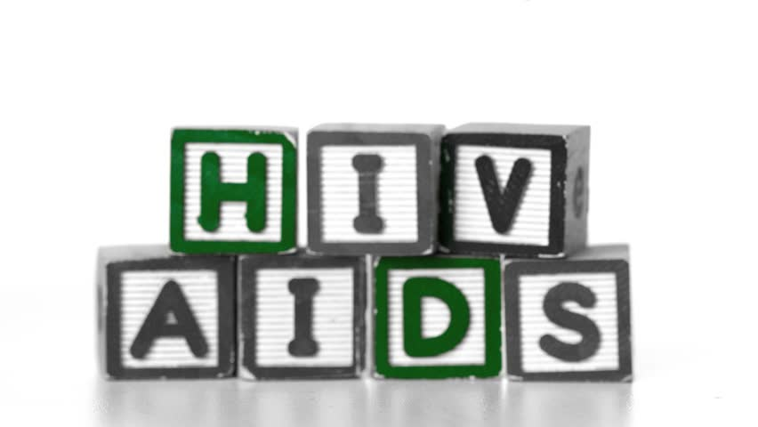 Needle falling in front of blocks spelling AIDS and HIV in slow motion - HD stock video clip