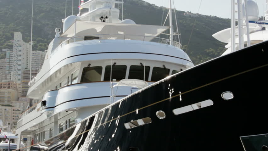 Close up view of Super Yachts moored in Port Hercules, Monaco.  Camera passes ahead of bow of two yachts. - HD stock video clip