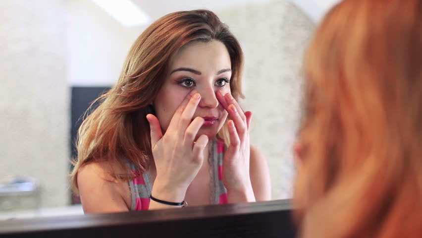 Beautiful young woman checking her face in the mirror